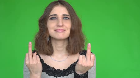 transação : Young woman showing middle finger gesture while looking at the camera over green background.