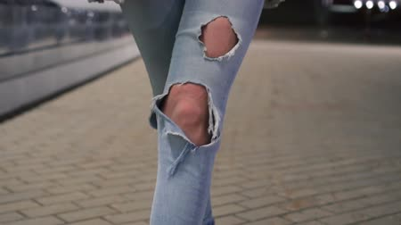 párat se : Shot of woman legs in ripped jeans walking on tile road. Urban Environment