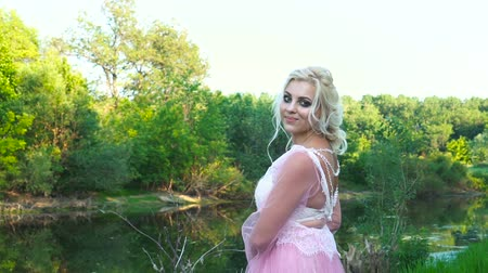libélula : Portrait of a beautiful girl in a pink dress near a river with makeup at sunset in summer.