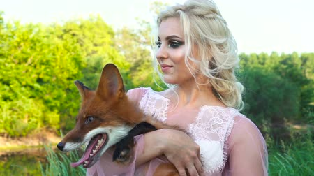 líska : A girl is holding her fox in her arms. The foxes is licked
