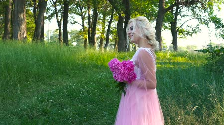 magenta flowers : Outdoor portrait of beautiful blond woman holding bouquet of pink roses Stock Footage