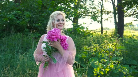 magenta flowers : Young blond woman in pink dress holds a bouquet of flowers, posing at camera.