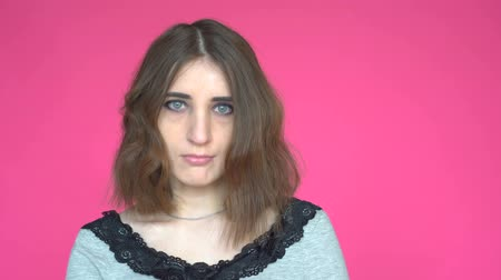 emin : Young woman says Yes, by shaking her head. Posing on pink background. Stok Video