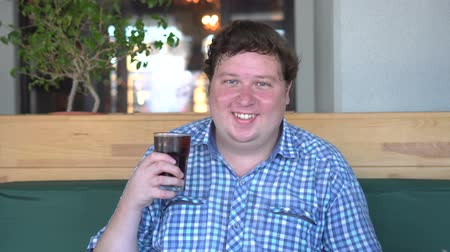 kola : Fat happy man holding a glass of soft drink cola and laughing, sitting in cafe. Beverage Stok Video