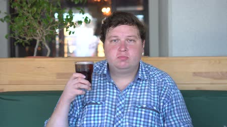 kola : Fat man holding a glass of drink cola sitting in cafe and chews food. Beverage