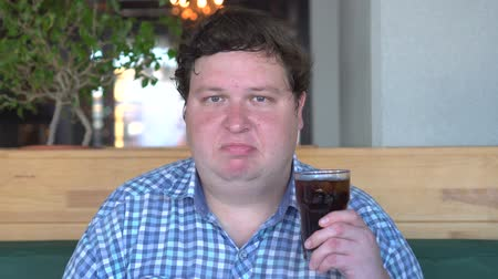coque : Fat man holds a glass of drink cola in cafe and saying no by shaking head Stock Footage