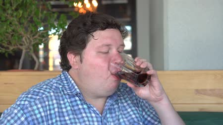 kola : Fat man in the cafe or restaurant drinking cola