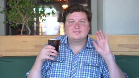 kola : Fat man holds a glass of drink cola in cafe and greeting, saying hello by waving hand