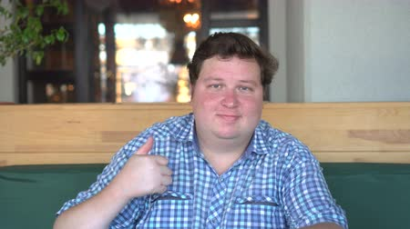 otuzlu yıllar : A handsome, fat man with big body shows thumbs up in the cafe or restaurant Stok Video