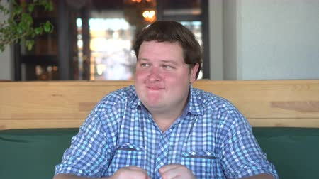 otuzlu yıllar : Handsome young white fat happy man waiting for something with great intrigue in restaurant