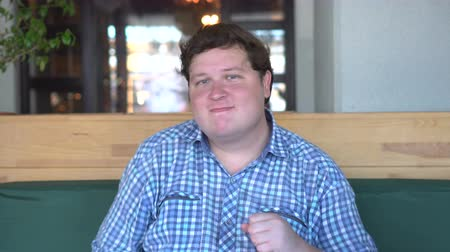 otuzlu yıllar : Handsome young fat man in shirt dancing in cafe or restaurant. Fat guy dancing sitting