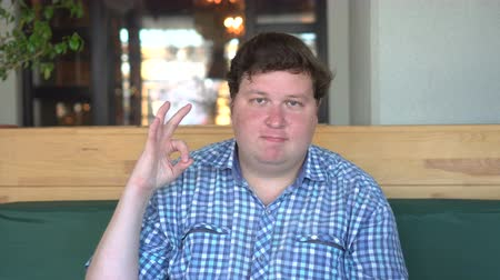 otuzlu yıllar : A handsome, fat man with big body shows okay sign in the cafe or restaurant