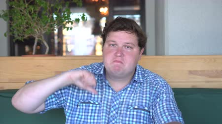 otuzlu yıllar : A handsome, fat man with big body shows thumbs down in the cafe or restaurant Stok Video