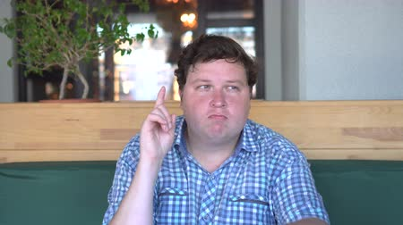 otuzlu yıllar : Portrait of a young fat man having idea and pointing finger up in cafe or restaurant