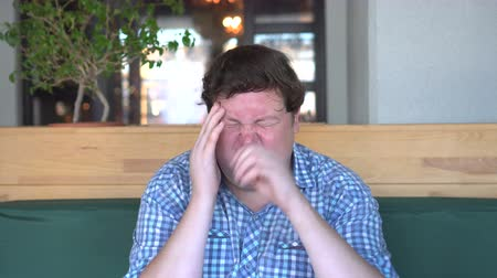 gergin : Headache or migraine. A young fat man holds his hands behind his head. Stok Video