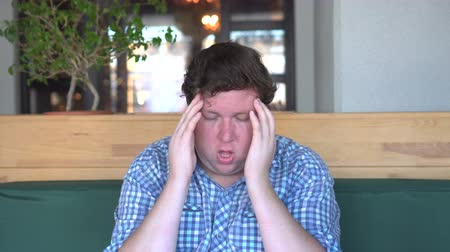 dor de cabeça : Headache or migraine. A young fat man holds his hands behind his head. Stock Footage