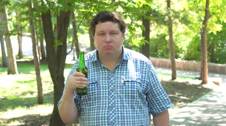 отвергать : Young man holding a beer and says no by shaking head, outdoor