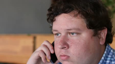 think big : Young tired man talking on phone indoor
