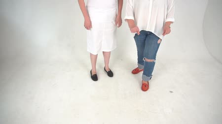 legs only : Two unrecognizable women dressed in jeans and dress on a floor isolated over white background.