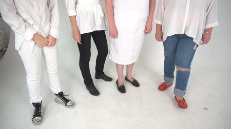 four legs : Four people dressed in jeans, dress, whete pants standing on a floor. isolated over white background Stock Footage
