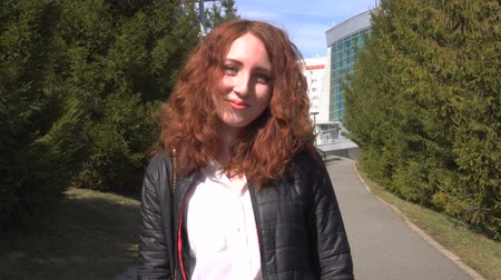 매력 : Portrait of a happy redhead girl with long hair looking at camera while standing outdoors.
