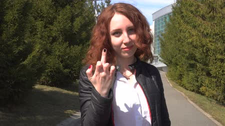 rude : Outdoor lifestyle close-up of a white sexy redhead lady show middle finger, fuck you off sign. Stock Footage