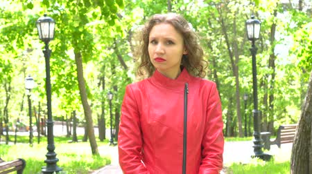 esteem : Attractive young woman in red jacket saying no by shaking head outdoors Stock Footage