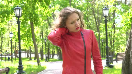 видя : Caucasian young woman standing outdoors has neck pain