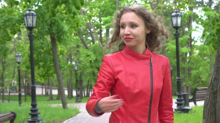 aliciamento : young woman in red jacket inviting someone to come in park. Vídeos