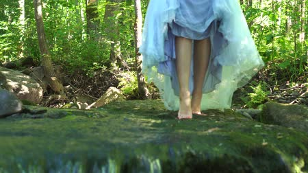 kapradina : Walking girl traveling in the wild jungle forest with a dress and steps over the ground over the clean mountain river. Dostupné videozáznamy