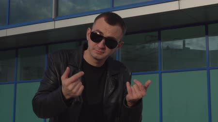 someone : young man in leather jacket and sunglasses standing outdoor and man inviting someone