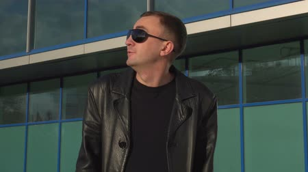 delighted : Young man in leather jacket and sunglasses surprised or confused, outdoor