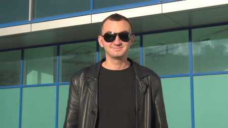 гангстер : Young man in leather jacket and sunglasses standing outdoor and smiles