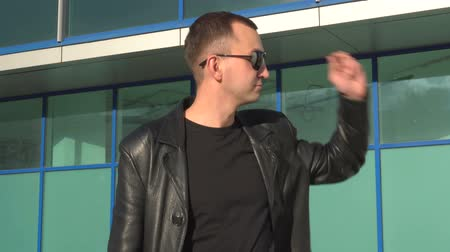 looking distance : Young man in leather jacket and sunglasses standing outdoor and looking away