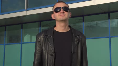 emin : Young happy man in leather jacket and sunglasses accepting offer by shaking head outdoor Stok Video