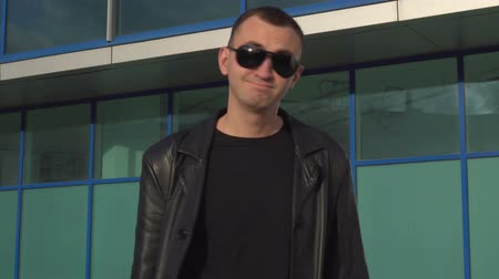 punker : Young serious man in leather jacket and sunglasses does not accept offer by shaking head outdoor