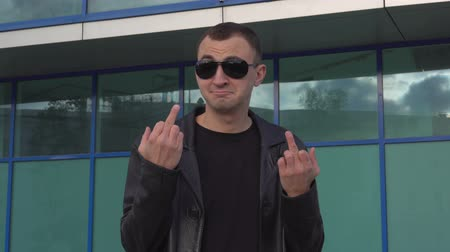rude : Young man in leather jacket and sunglasses standing outdoor and showing middle finger.