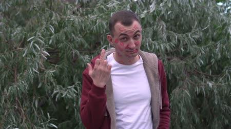 rude : Young man with face full of lipstick marks of kisses is showing middle finger Stock Footage