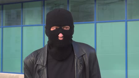 villain : Criminal man thief or robber in mask makes funny faces in balaclava