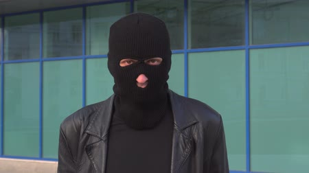 villain : Criminal man thief or robber in mask looking at camera Stock Footage