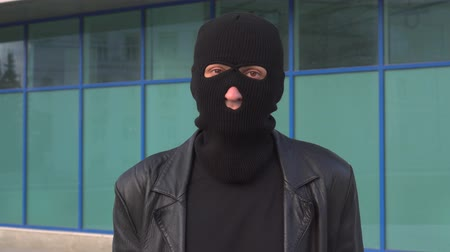 villain : Criminal man thief or robber in mask says Yes, by shaking his head. Portrait of man in balaclava