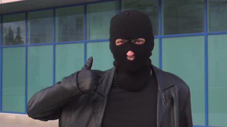 villain : Criminal man thief or robber in mask shows thumb up.