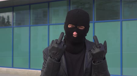 transação : Criminal man thief or robber in mask showing middle finger at camera.