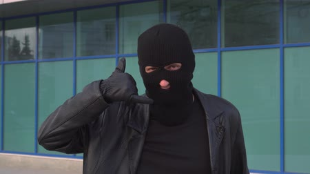 villain : Criminal man thief or robber in mask showing call gesture by his fingers.