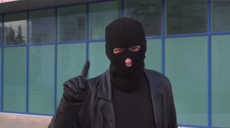 villain : Criminal man thief or robber in mask is disapproving with hand sign make negation finger gesture.