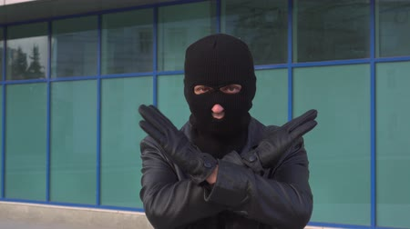 refus : Criminal man thief or robber in mask is showing stop sign gesture by crossing his hands.