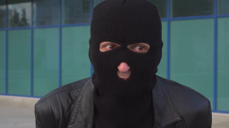 balaclava : Worried criminal man thief or robber in mask is waits something.