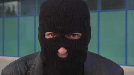 villain : Close up portrait of criminal man thief or robber in mask looking at camera.
