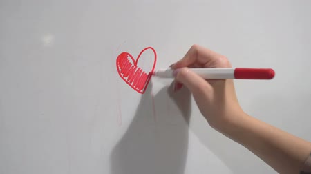 ponta : Female hand with felt-tip marker paint draws the heart on plastic board.