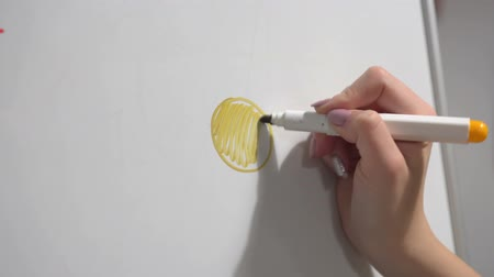 ponta : Female hand with felt-tip pen quickly draws sun on plastic board